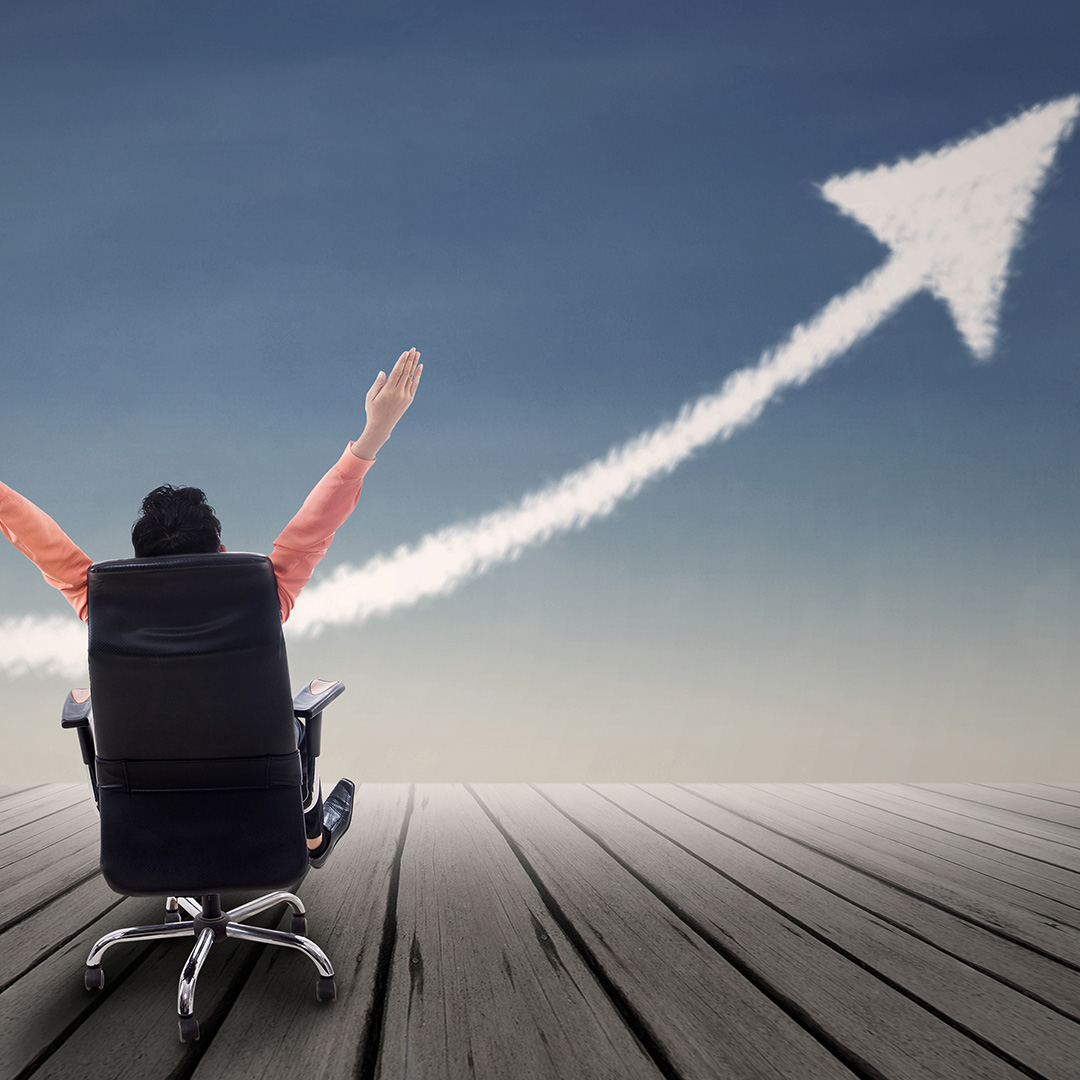 Businessman sitting on chair with raised arms and up arrow signal