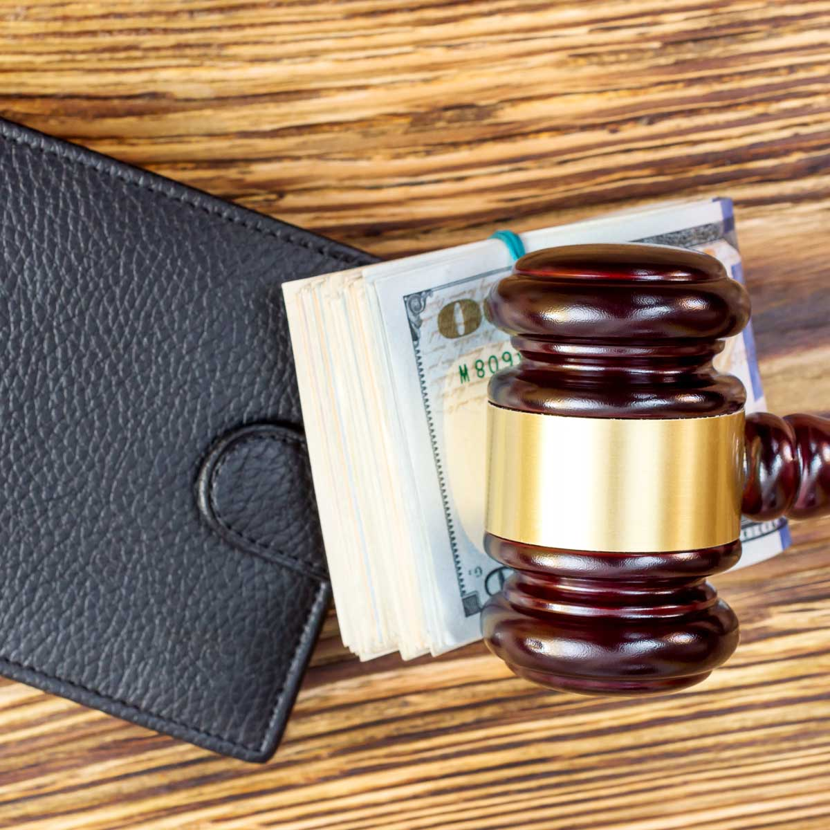 A gavel on a stack of cash on a wallet
