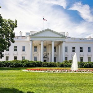 The White House on a summer day with the American flying over it.