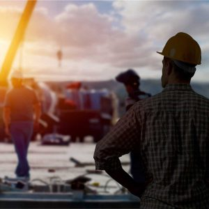 a construction worker looking out at the project he is working on; sun is setting in the background