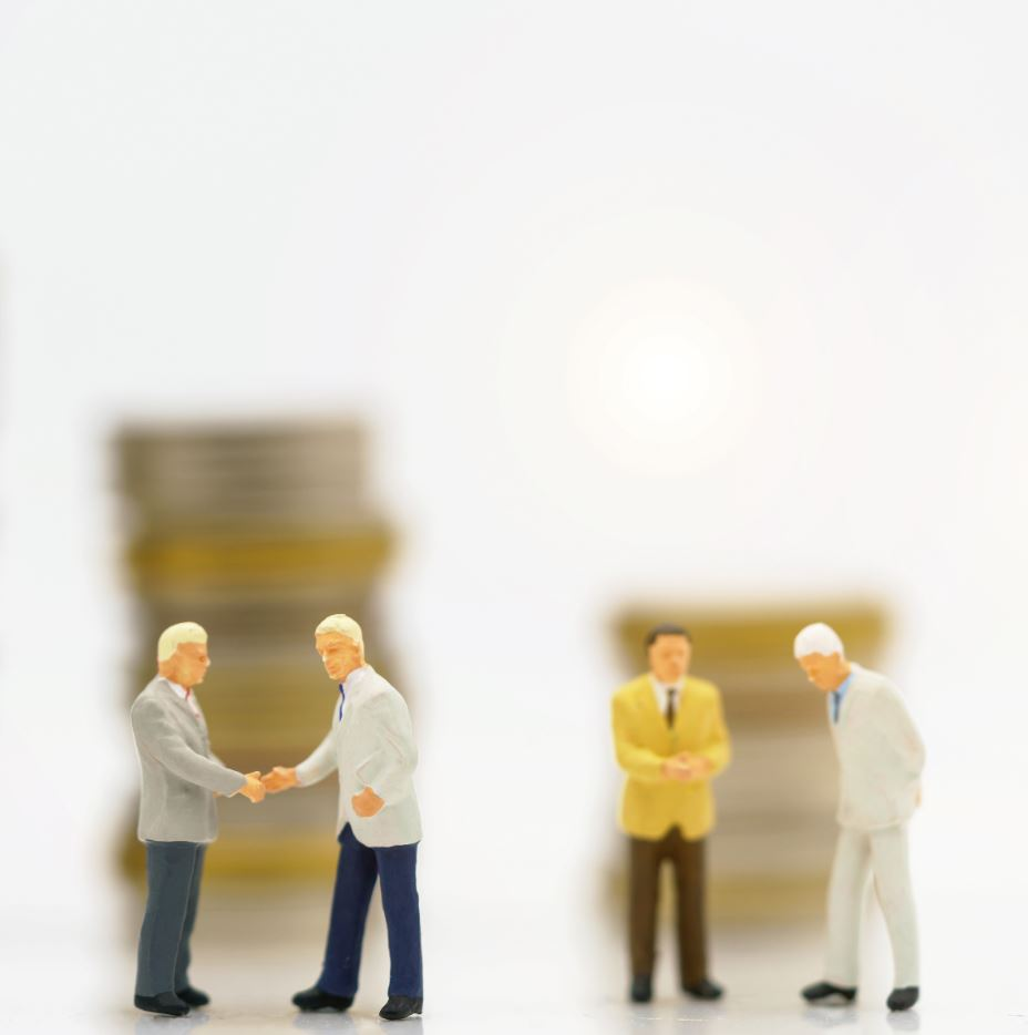 Miniature people: Businessman handshake to business success with coins stack. Commitment, agreement, investment and partnership concept