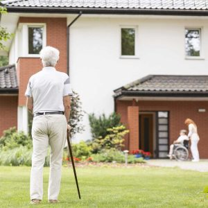 an image of a senior living center with an elderly man and a cane standing in front of it