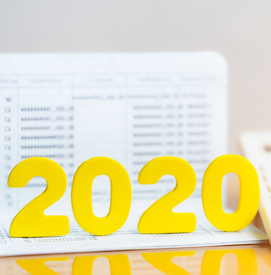 Wood block 2020 on bank passbook with calculator. Concept of income and budget planning for year 2020.