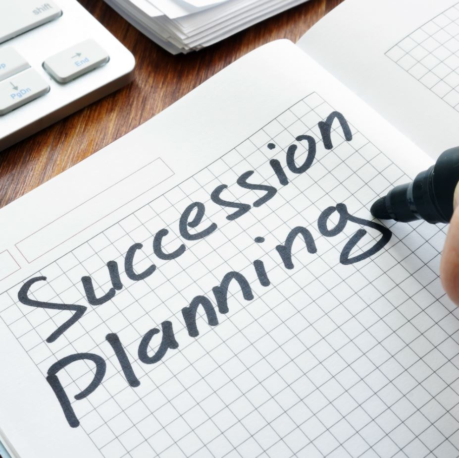 Man is writing succession planning in the book