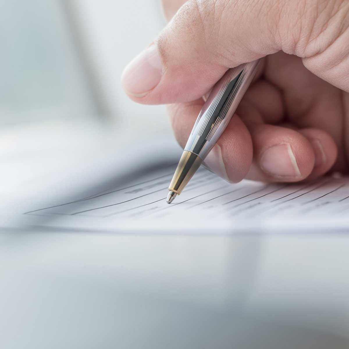 employer writing on a form with a pen. close up of hand and form