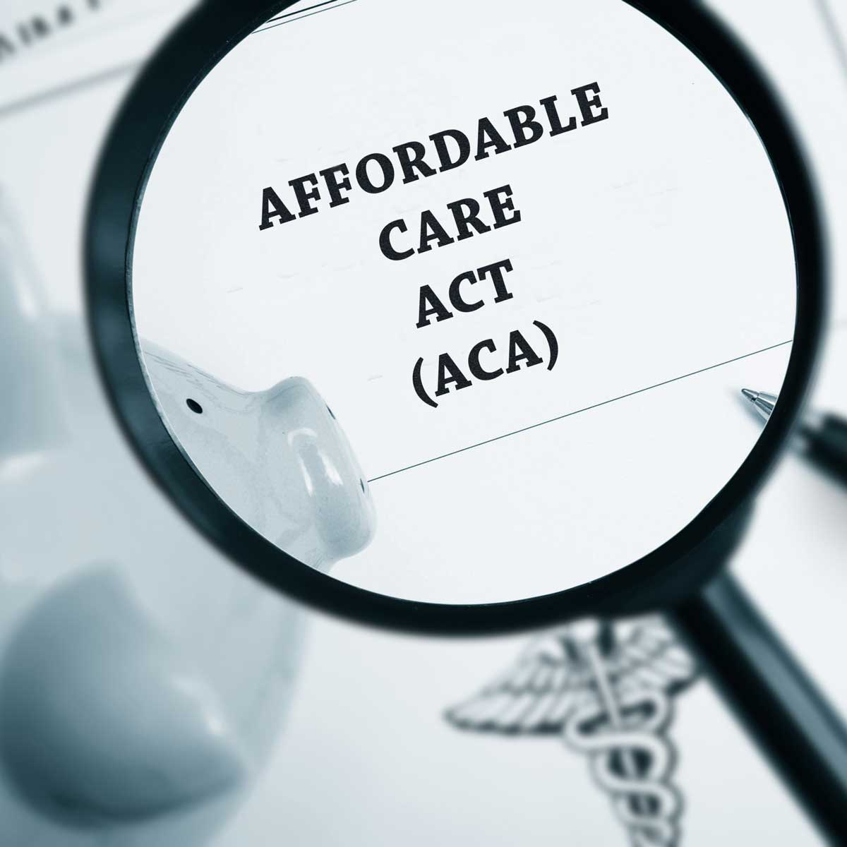 a magnify glass over a black and white paper that states affordable care act (ACA) and a piggy bank, pen, and healthcare imagery