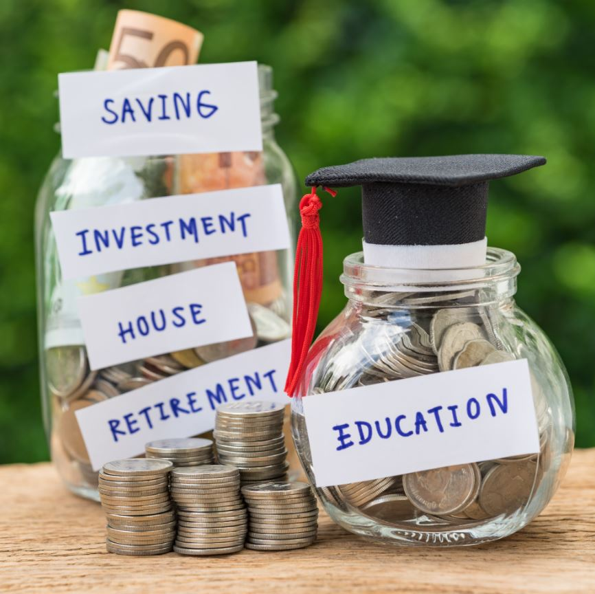glass jar with full of coins and graduates hat label as Education with stack of coins as education or savings concept