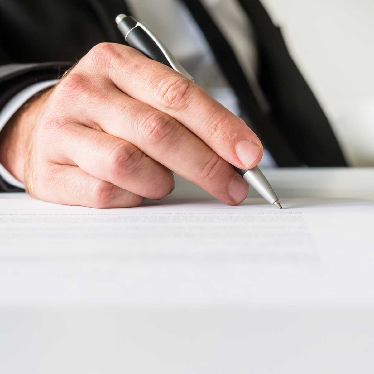 image of businessman sitting at his office desk signing a document