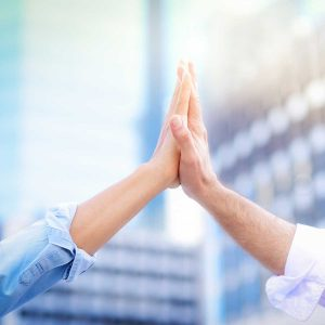 Cloe up of both hands giving high five to each other With a blurred building background, in the concept of successful business collaboration and teamwork