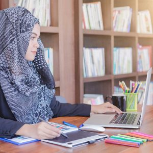 young creative designer woman using pen tablets and laptop in front of bookshelf.