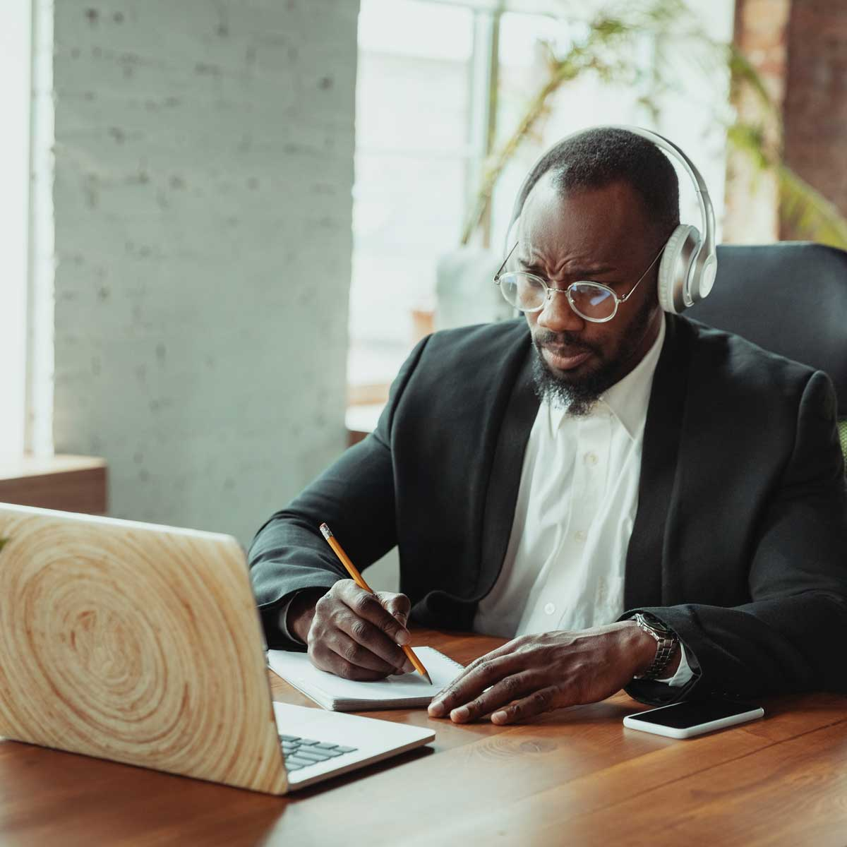 Businessman or student working from home being isolated or keep quarantine 'cause of coronavirus. African-american man using laptop, tablet and headphones. Online conference, lesson, remote office.