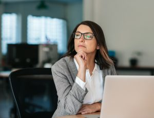 Business woman thinking about work while sitting at her office desk
