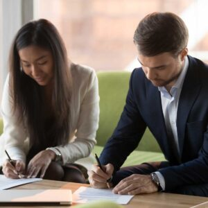 businesswoman and businessman sign contracts documents at meeting, male female business partners client and service provider put signature on legal papers making agreement