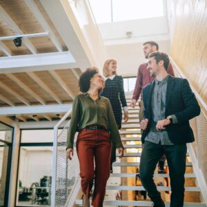 group of employees walking down steps in office and conversing