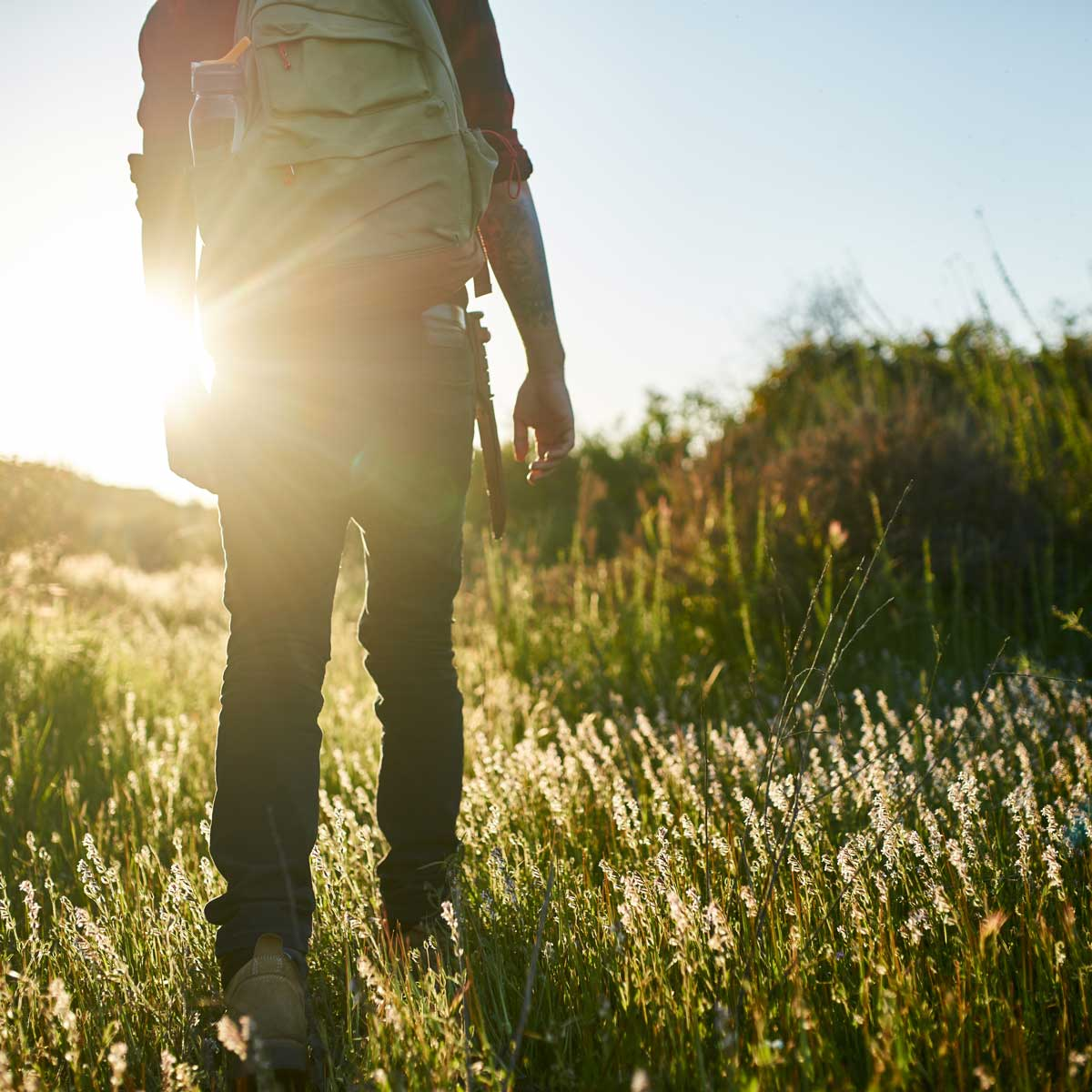 male hiker walking through grass in southern california during sunset