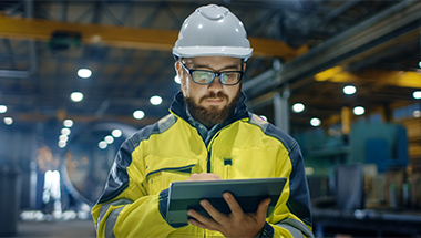 Industrial Engineer in Hard Hat Uses Touchscreen Tablet Computer
