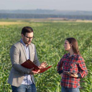 Businessman and farmer talking in field