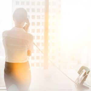 businesswoman talking on landline phone while standing at office