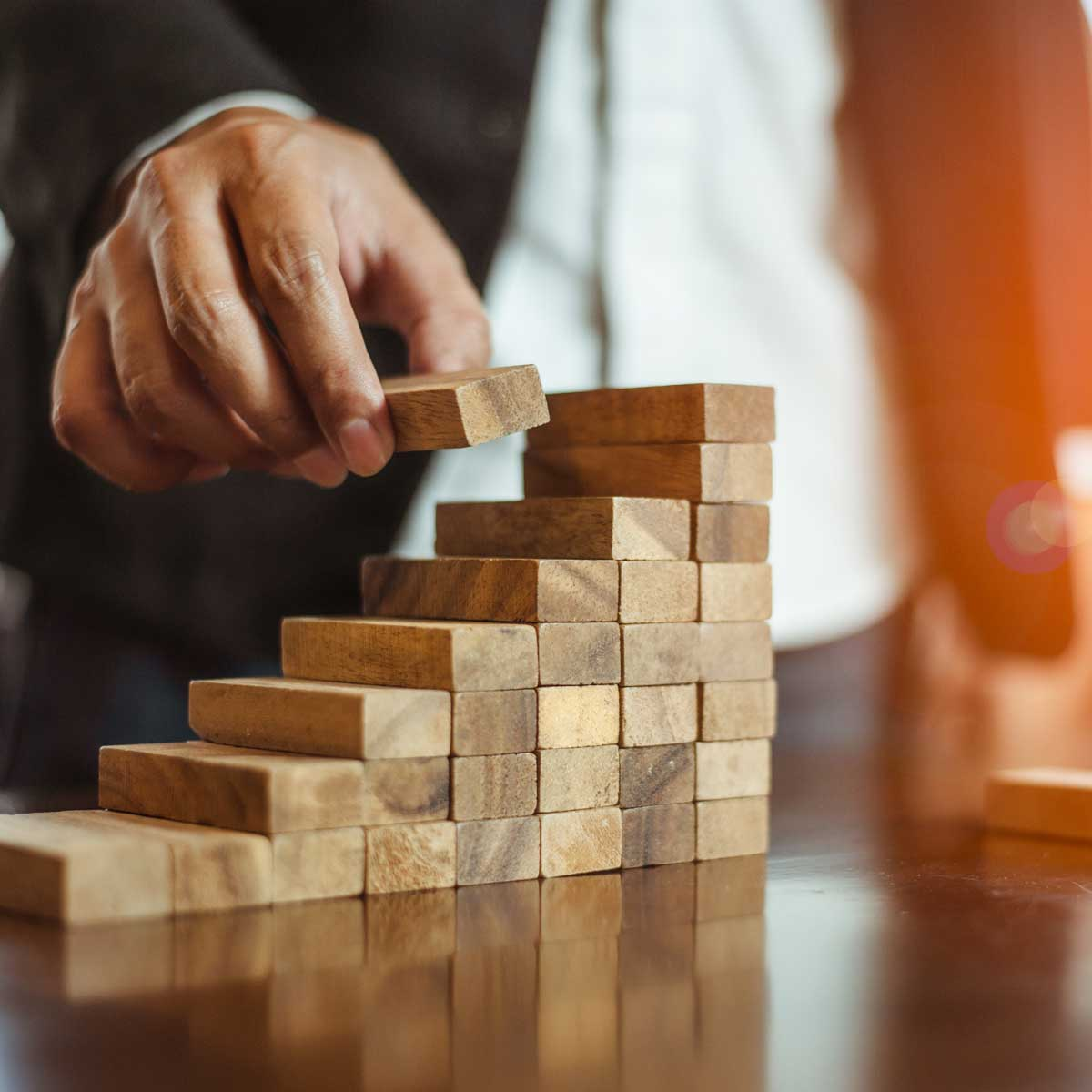 plan and strategy in business. hand of man has piling up and stacking a wooden block. Businessman Building The Success.