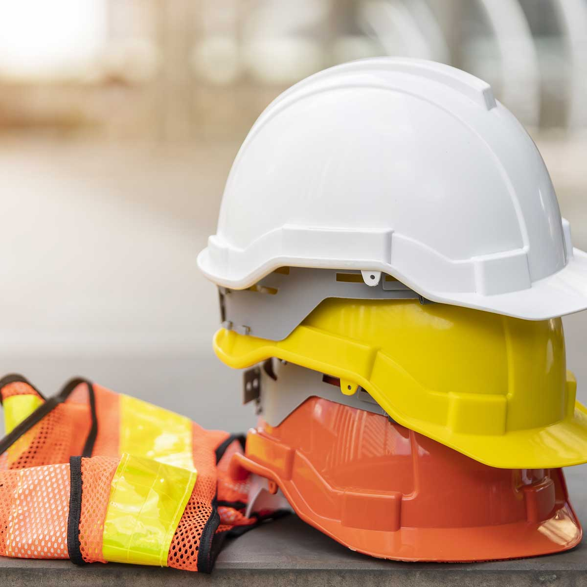 safety first project of workman as engineer or worker or crew and insurance, business concept. construction safety gear including a white, yellow and blue hard safety helmet on concrete floor on city