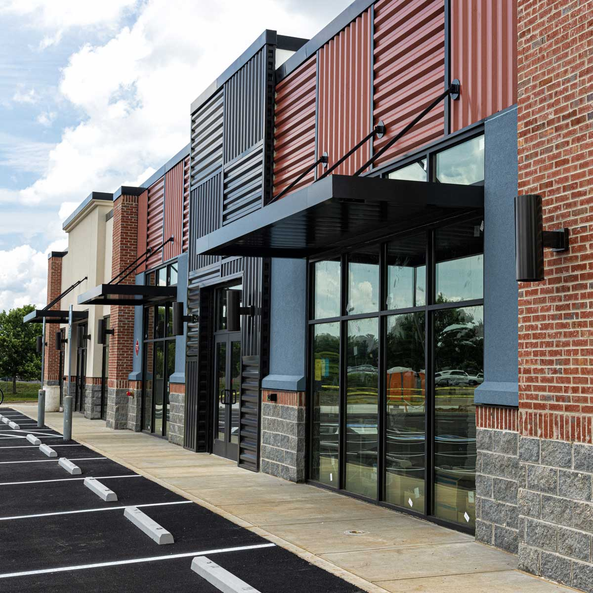 brick building exterior; strip building with parking lot