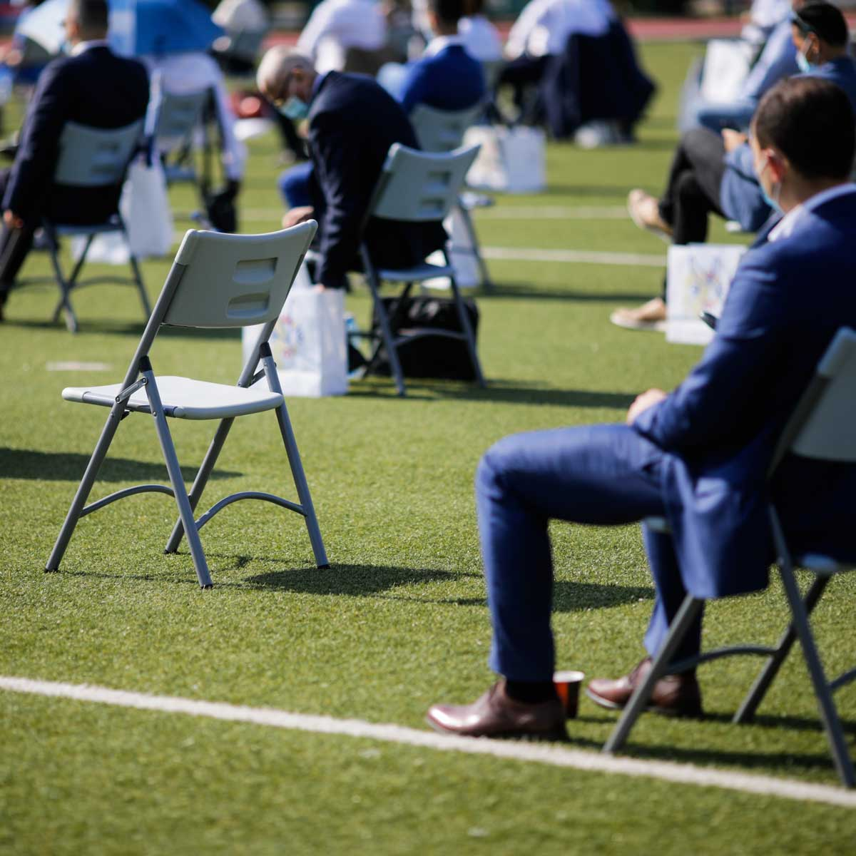 People sit on chairs apart one from another to maintain the social distance during the Covid-19 outbreak at an outdoor event on the turf of a stadium.