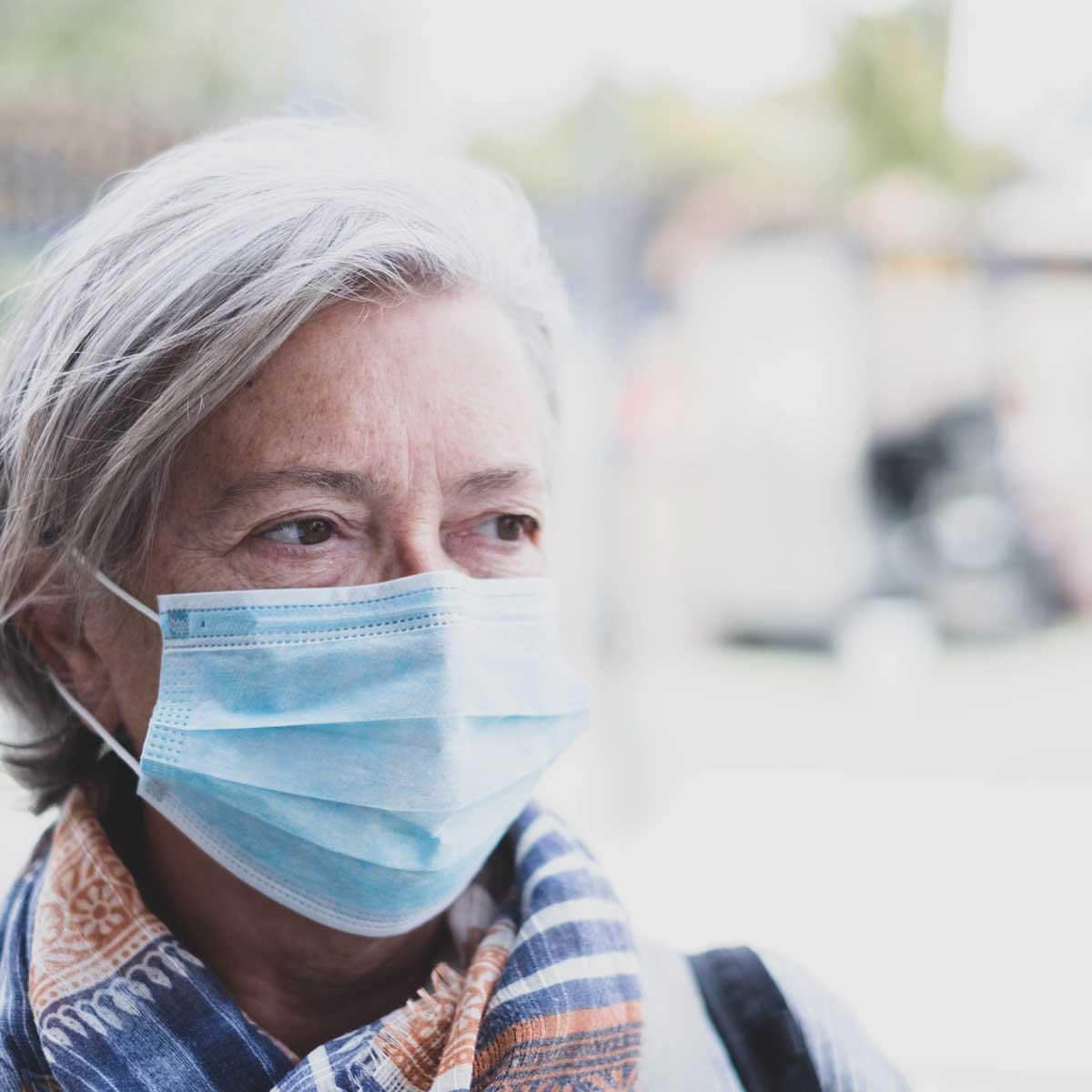 close up of face of mature woman looking away wearing medical mask prevention coronavirus or covid-19