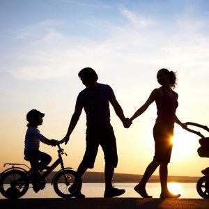 happy traditional family walking on sunset