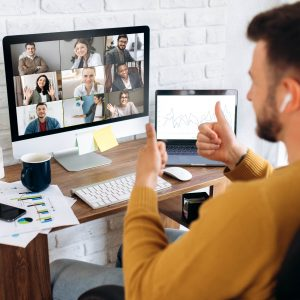 Employee in a video call with teammates giving a thumbs up