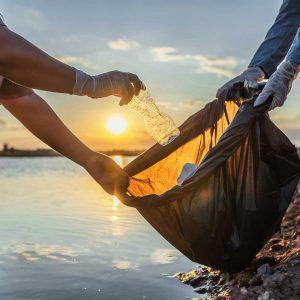 stewardship and community; people volunteer keeping garbage plastic bottle into black bag on river in sunset