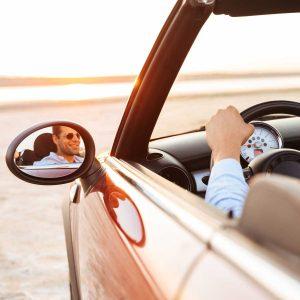 Photo of joyful man driving convertible car by seaside at sunrise