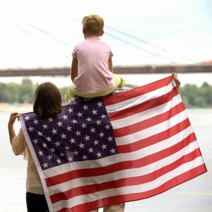 Family wrapped in American flag looking at bridge, immigration for better life
