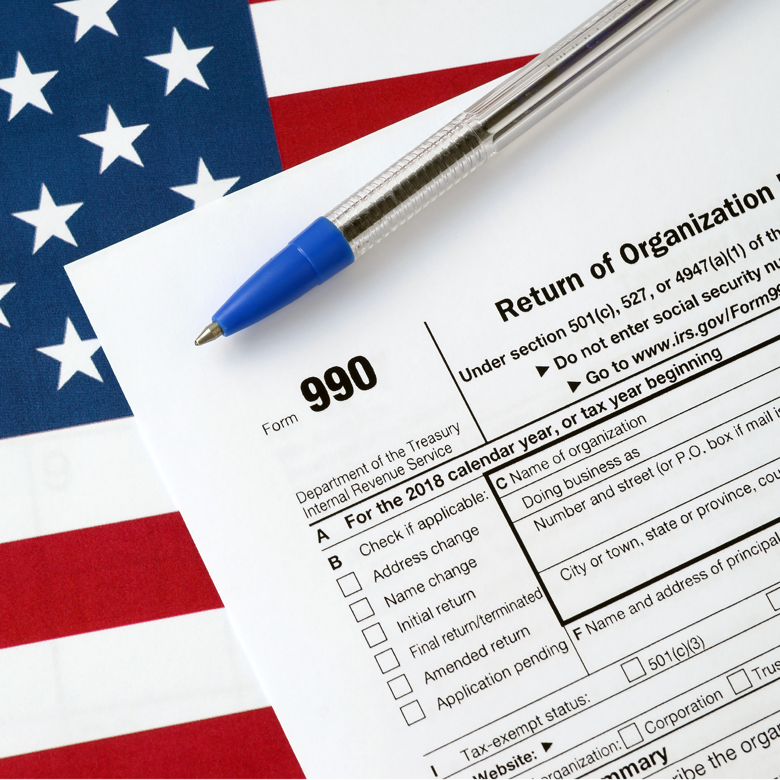 Form 990 Return of organization exempt from income tax and blue pen with dollar bills lies on office calendar. Internal revenue service tax form
