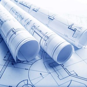 The part of architectural project; blueprint imagery; three rolls of blueprints laying on top of a flattened blueprint