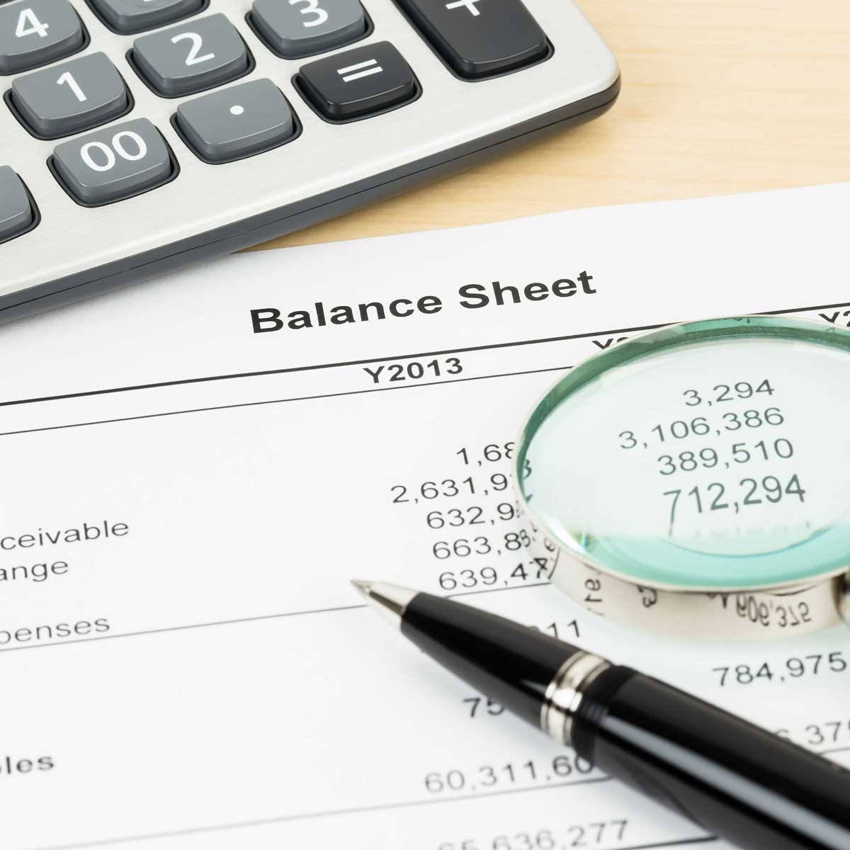 Balance sheet financial report with magnifier, pen, and calculator