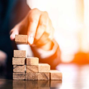 plan and strategy in business. risk concept. hand of man has piling up and stacking a wooden block. Businessman Building The Success.