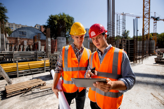 construction workers discuss a building project on a tablet