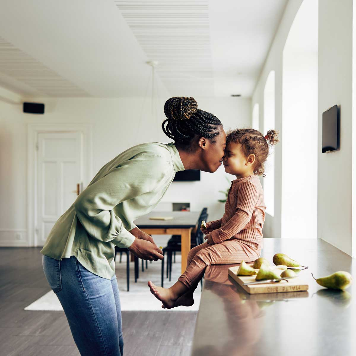 mom and her little girl having a snack at home; loving mother kissing little daughter who is sitting on kitchen counter with snack of pears next to her