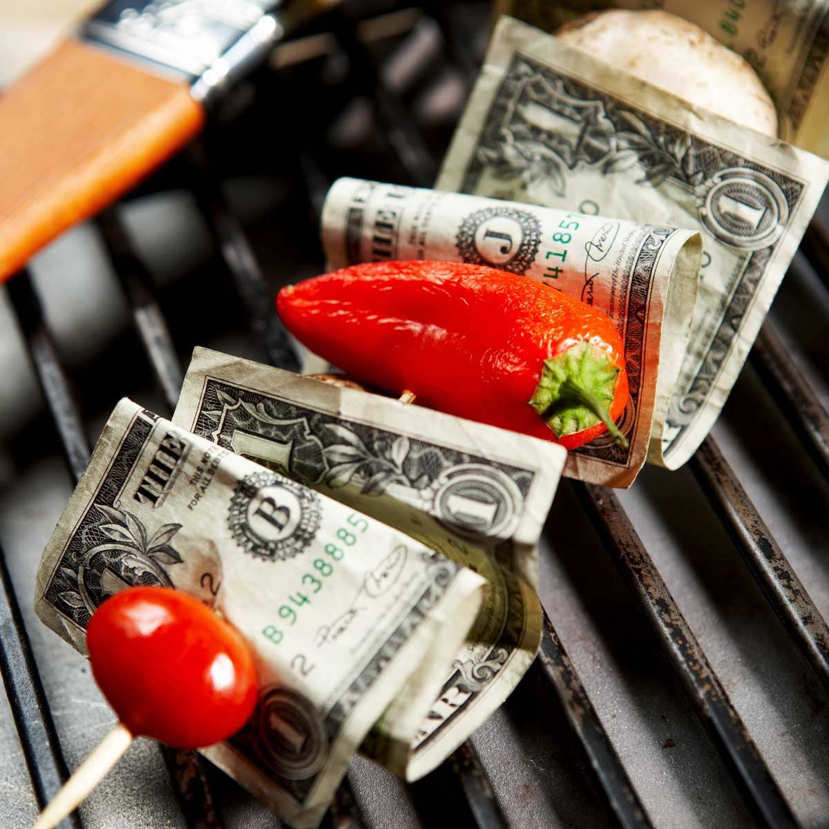 grilling and bbq concept; grilling skewer with tomato, pepper and dollar bills on the stick