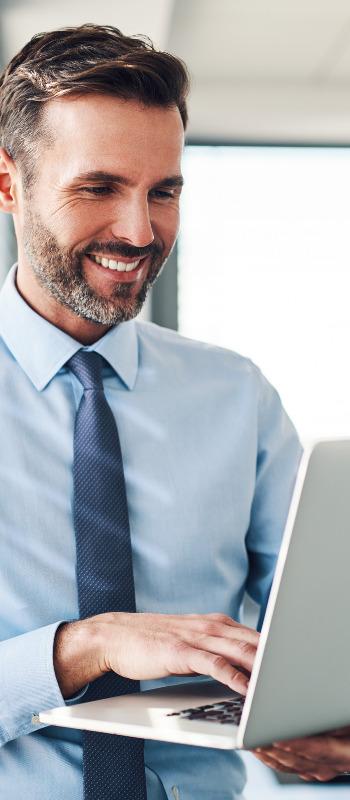 Businessman in modern office looking on laptop