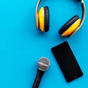 blogger, journalist work space with microphone, telephone and headphones on blue background top view mock-up