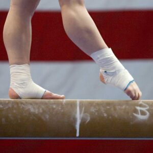 Closeup of a gymnast's feet with chalk and protective equipment in a gymnastics competition.