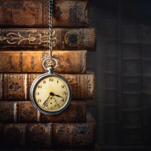 Vintage clock hanging on a chain on the background of old books. Old watch as a symbol of passing time. Concept on the theme of history, nostalgia, old age. Retro style.