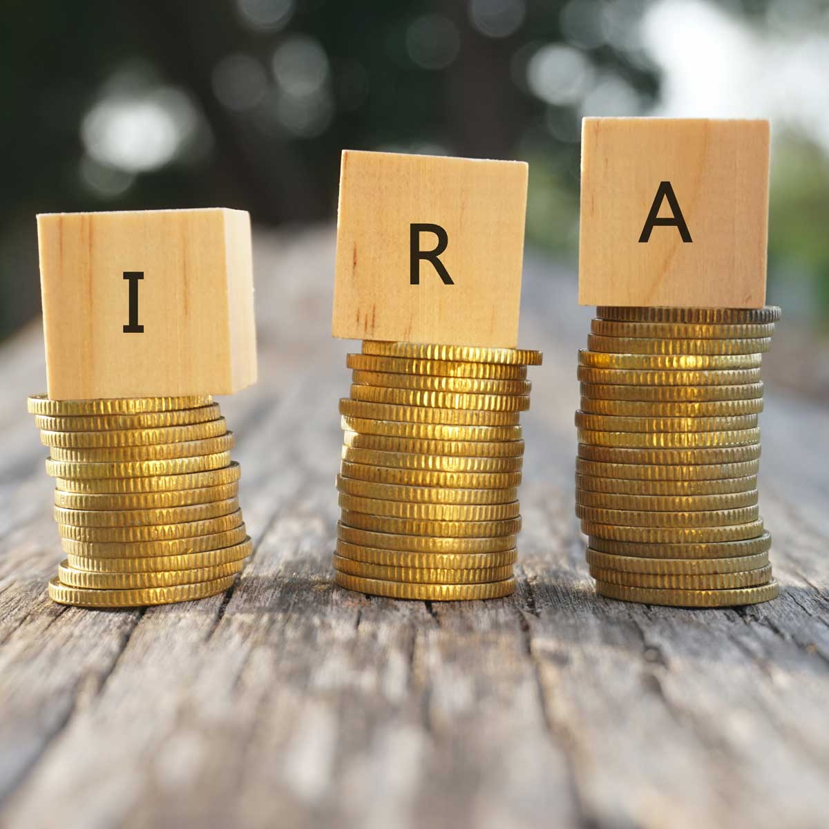 Close up of stacking gold coins and wooden blocks written IRA on nature background and natural lighting. Individual Retirement Account concept