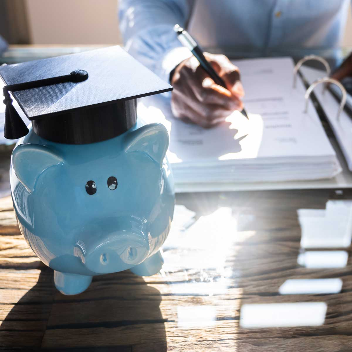 Student Loan. Accounting Advisor concept; image of a blue piggy bank with a graduation cap on it as the main focus with a businessman in the background calculating rates on a note pad