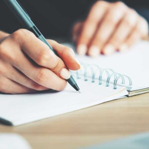 Woman writing in notepad; image focused on hand holding the pen on top of the spiral notepad