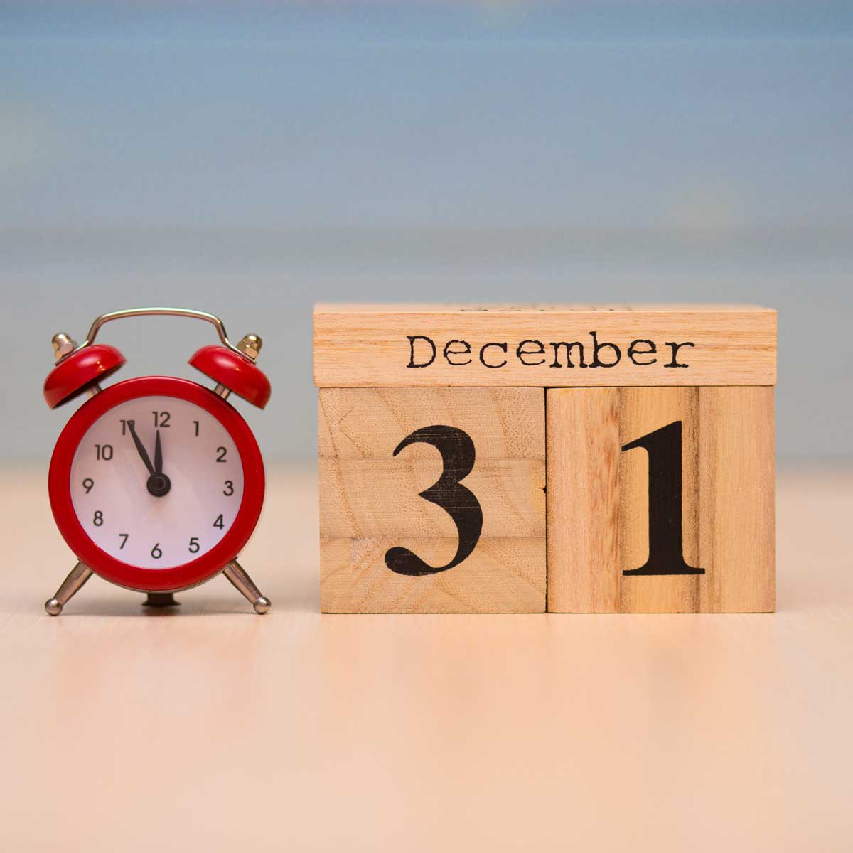 December 31st set on wooden calendar and red alarm clock with blue background.