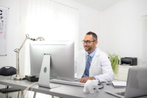 portrait of a handsome man male doctor in medical practice office working on computer
